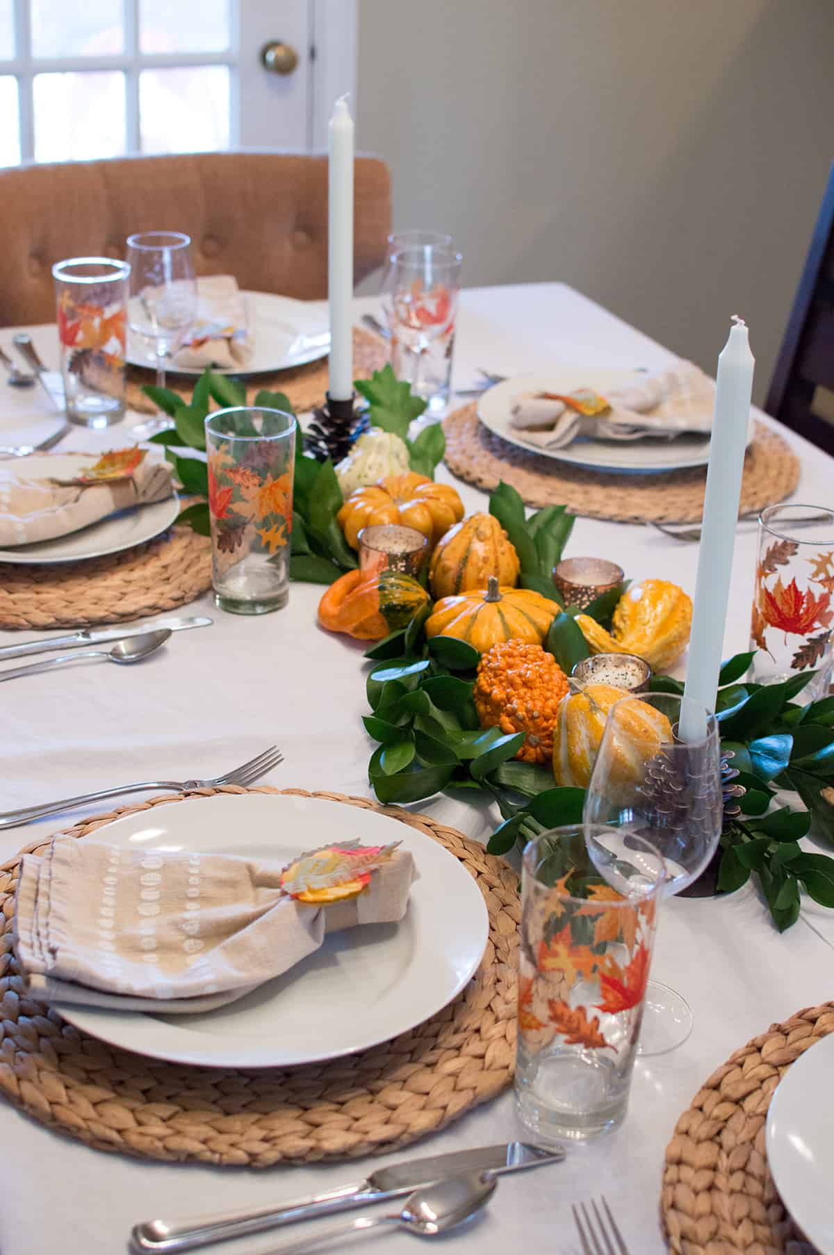Loving the pop of color of the centerpiece against the neutral place settings on this Thanksgiving Tablescape