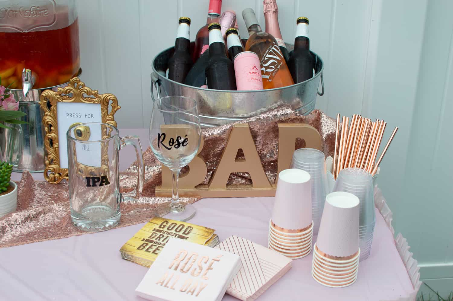 Set up a cute bar for a rosé wine bridal shower with rose gold party supplies