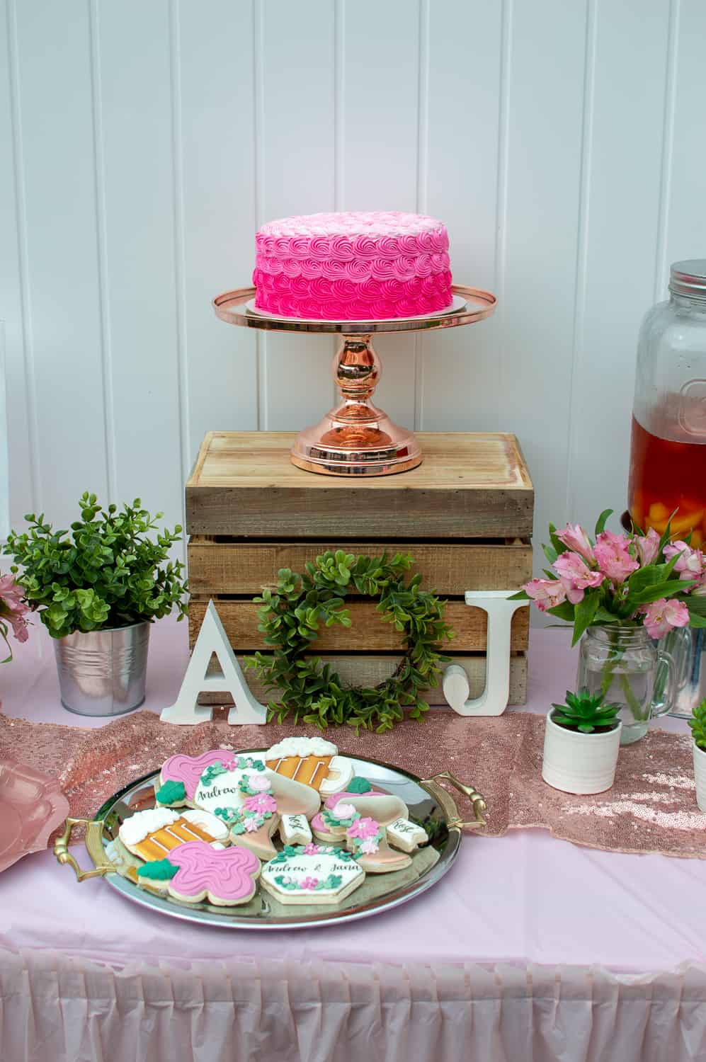 Pink rosette cake on Amalfi Decor cake stand and custom sugar cookies