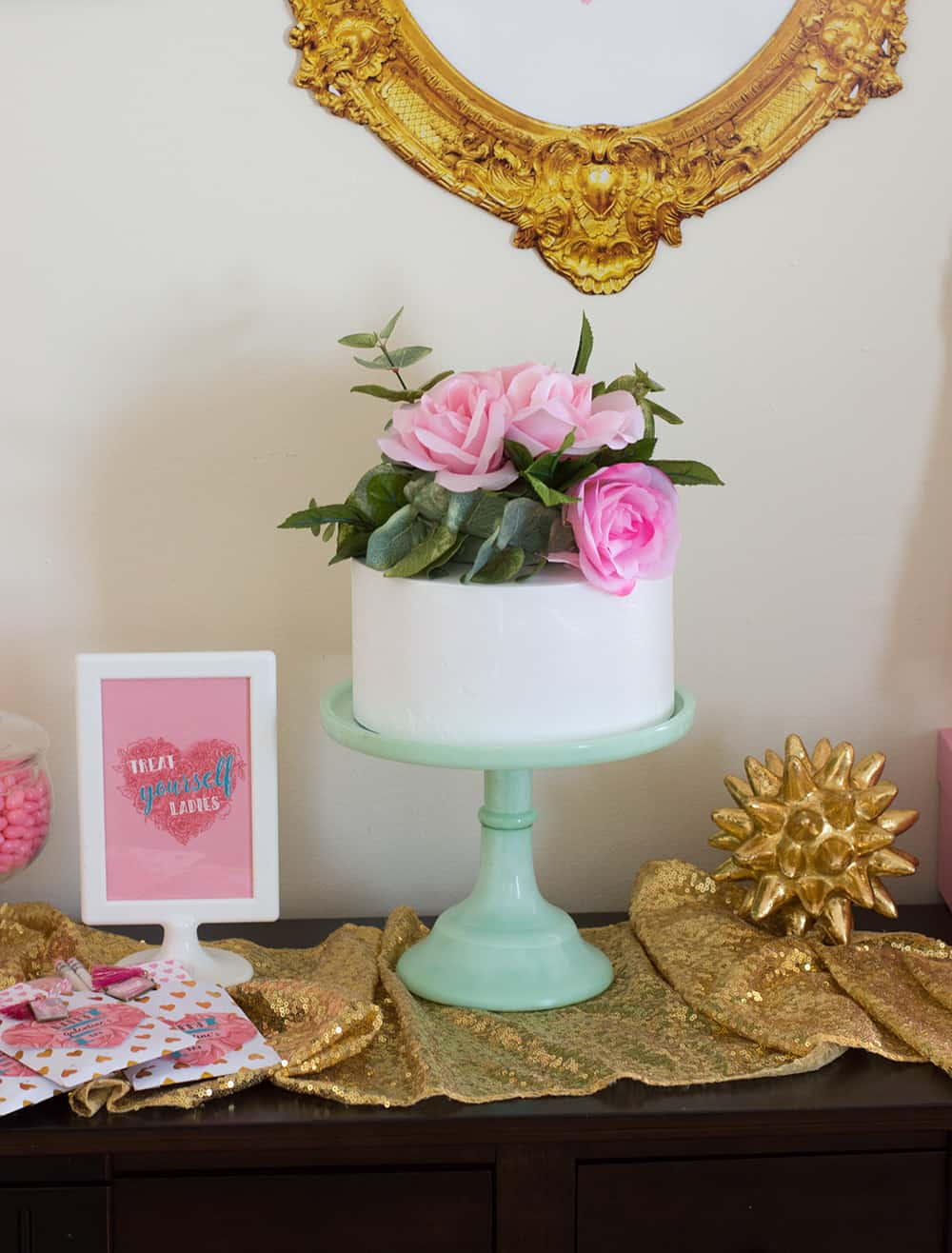 White cake topped with DIY faux flower cake topper on mint stand