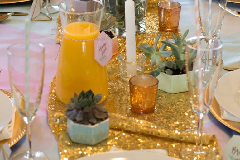 Flowers, succulents, and candles create a simple yet breathtaking centerpieces, especially when layered on top of gold.