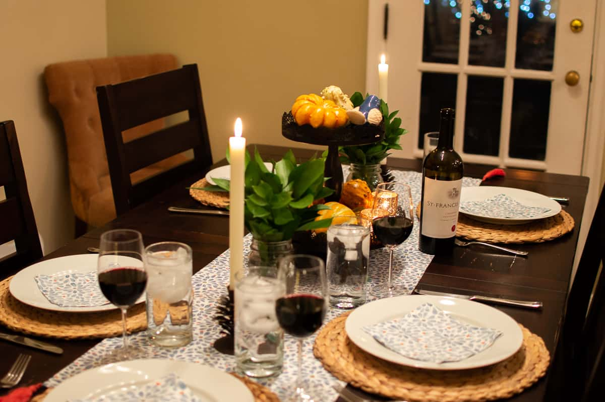 Fall tablescape with glowing ambient light from candles create a cozy atmosphere for a dinner in.
