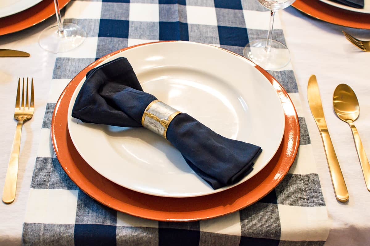Thanksgiving place setting with orange charger and blue napkin