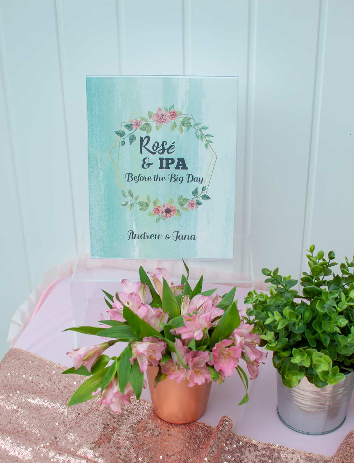 Rosé and IPA party sign along with flowers and greenery
