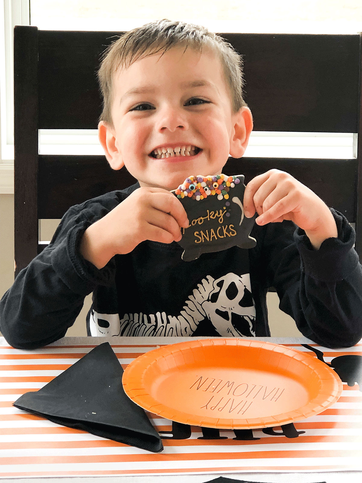 smiling child with Halloween sugar cookie