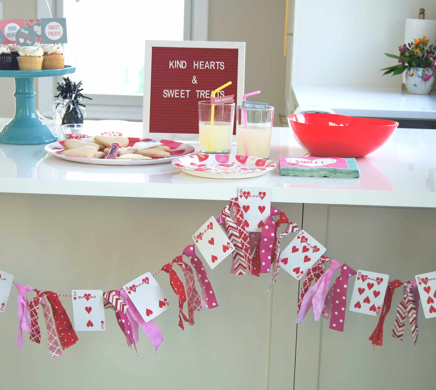 Valentine's play date food table with cupcakes, popcorn, and lemonade